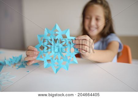 Making of snowflakes from blue paper.  A traditional Christmas arts and crafts project
