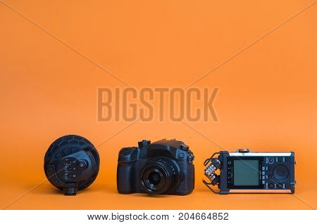 equipment for field video production, camera, microphone, recorder on orange background