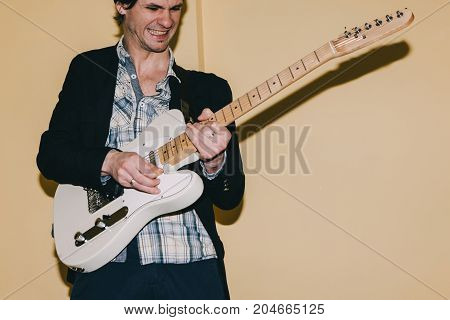 Adult guitarist enthusiastically playing guitar. Creative hobby for grown ups, music concept