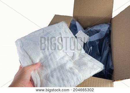 Woman's hand unpacking / unboxing cardboard carton box with women's dresses inside after buying ordering online via internet Female inspects the garments goods isolated on white with clipping path