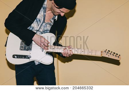 Grown up guitarist enthusiastically plays guitar. Creative hobby for males, music concept