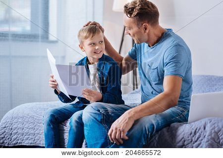 Well done. Proud loving father patting his little son on the head while he studying new material from several printouts