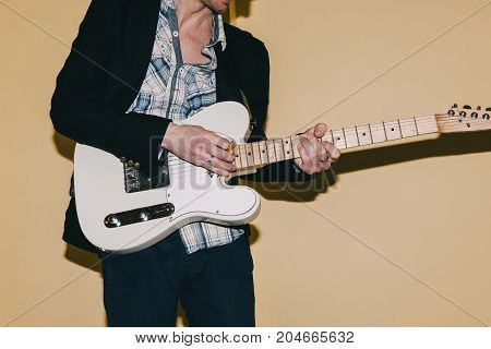 Hipster guitarist playing electric guitar. Unrecognizable male musician, repetition in studio, music concept poster