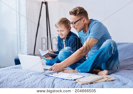 Easier together. Cheerful pre-teen boy sitting on the bed next to his father and making notes while watching educational videos with his father