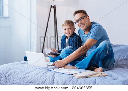 Quality time. Handsome cheerful man sitting on the bed next to his little son making notes and studying together with him, both of them looking at the camera and
