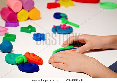 Kids hands molding modeling clay or plasticine on white table