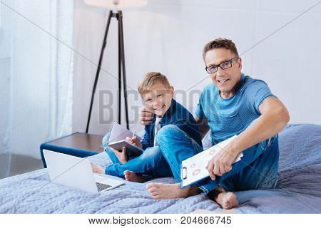 Family ties. Upbeat middle-aged man and his little son sitting on the bed and bonding to each other while studying together