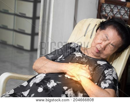 elderly asian woman sitting on a chair at living room with heart attacks.Both woman's hands on breast because of hard breathing Face old woman with pain caused by heart disease.