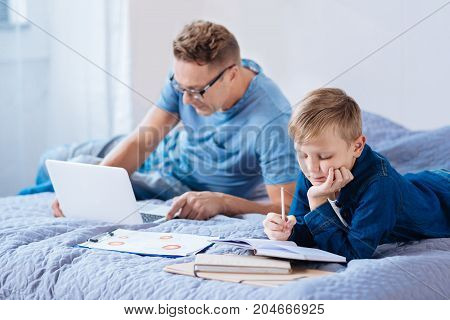 Busy bees. Charming little boy lying on the bed next to his father and doing his math assignment while his father working on the laptop