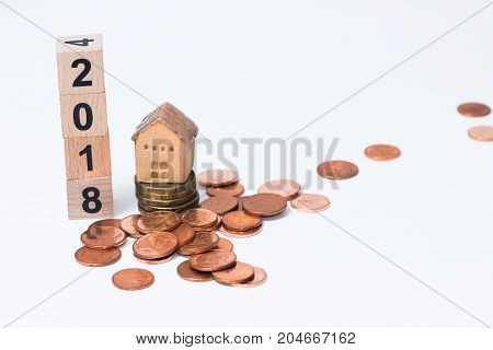 The wooden cube for new year with the house model and Thai coins on white background