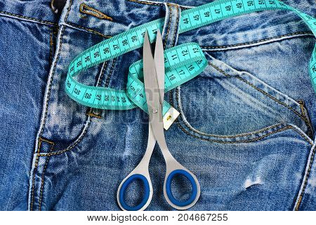 Jeans belt loops zipper and pocket close up and top view. Tailors tools on denim textile. Metal scissors and blue measure tape on jeans. Making clothes and design concept.