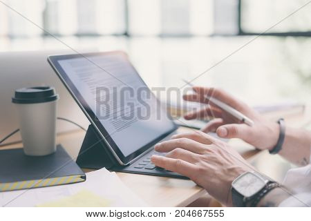 Businessman working at office.Closeup view of male hands typing on electronic tablet keyboard-dock station. Business text information on device screen.Horizontal.Blurred background