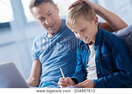 Great job. Proud loving father patting his beloved son on the back while the boy succeeding in doing math home assignment