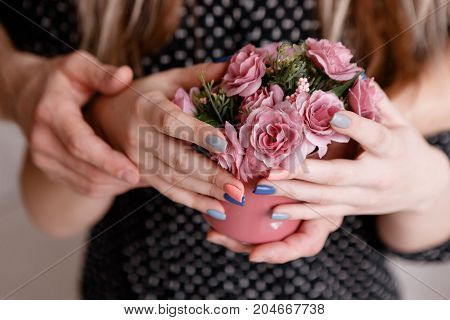 Embracing man and woman hold roses in crimson cup together. Sensitive concept of gift with love, romantic proposal, close relationship between people