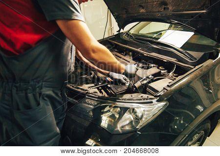 Car engine repair. An auto mechanic fixing an engine