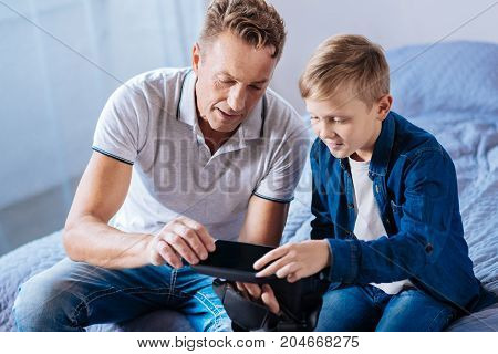 Brand new device. Cheerful curious father and his little son sitting on the bed and inspecting their new VR headset, scrutinizing it thoroughly