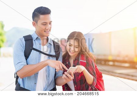 Happy Asian couple traveler holding use a smart phone at train station waiting for train in vacation time;Traveler Concept