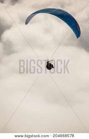 Paragliding in the snowy mountains with clouds