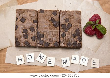 Chocolate brownie slices with raspberries and the word home made