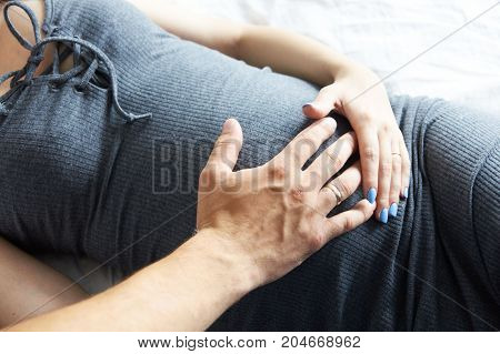Pregnant girl. Motherhood. Father and mother touch