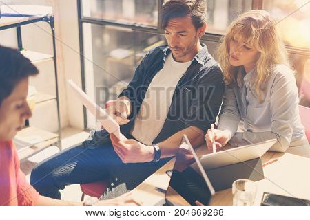 Group of three young coworkers working on laptop computer at sunny office. Woman holding paper documents and pointing on notebook screen. Horizontal.Blurred background