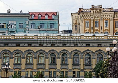 fragment of city houses with windows and roofs against the sky