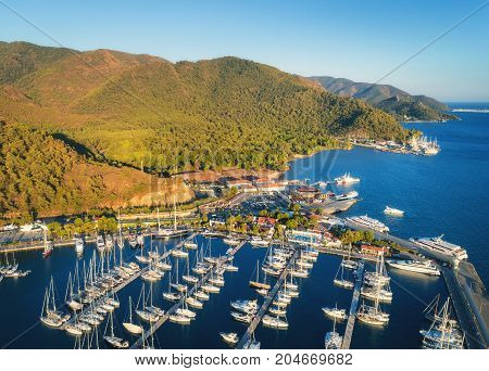Aerial view of boats and beautiful mountains at sunset in Marmaris, Turkey. Colorful landscape with boats in marina bay, sea, city, forest. Top view from drone of harbor with yacht, sailboat. Travel