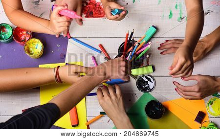 Artists Hands With Stationery And Colored Paper. Hands Hold Markers