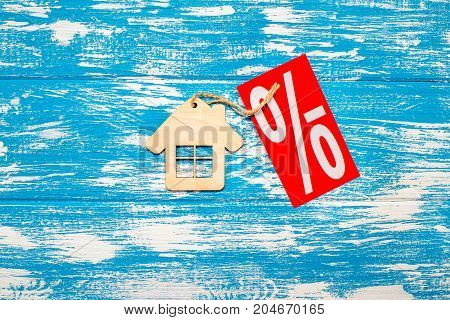 The symbol of the house lies on a blue wooden background