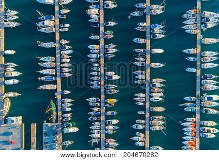 Aerial view of amazing boats at sunset in Marmaris, Turkey. Minimalistic landscape with boats and sea in marina bay. Top view from drone of harbor with yacht, motorboat and sailboat. Beautiful port