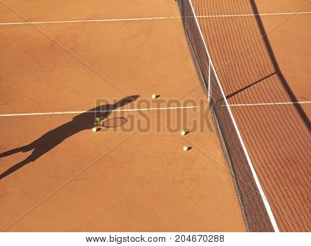 Shadow of tennis player at net with scatttered tennis balls on clay court