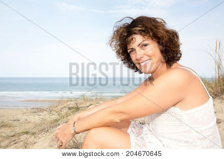 Close-up Portrait Of Smiling Female By The Sea. Happy Woman Standing At The Seaside And Looking Away