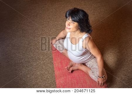Pregnancy Yoga and Fitness concept. Healthy maternity lifestyle concept. 40 week pregnant middle aged caucasian woman sitting in asana doing yoga exercise. Top view dark colore copy space.