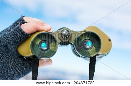 Man Using Binoculars On Snow Covered Mountain