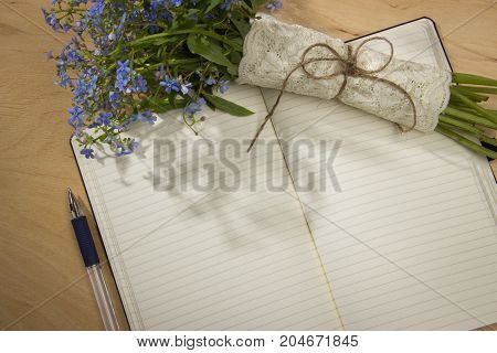Spring bouquet of forget-me colors in the morning rays of the sun notebook and pen on the wooden table