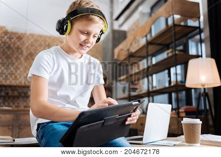 Favorite songs. Upbeat pre-teen boy sitting on the table in the study, listening to the music and using his tablet to create a playlist of favorite songs