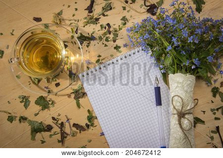 Spring floral bouquet of forget-me and a cup of tea in the morning sun on the notebook on the wooden table
