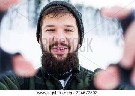 Bearded Man Taking Selfie On Snowy Mountain
