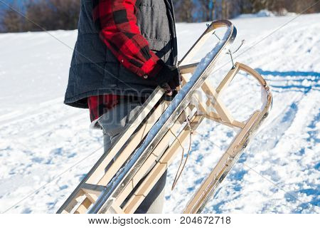 Man Carrying Sleights Up Snowy Mountain