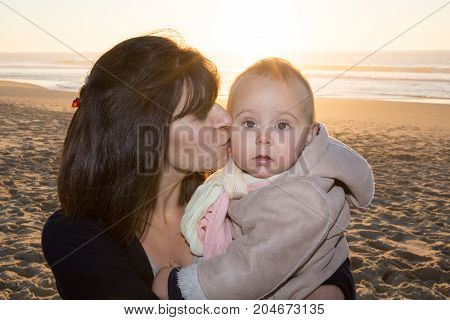 Mother And Child Are Hugging And Having Fun Outdoor In Sand Beach In Winter
