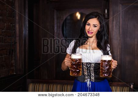 Woman wearing a traditional Bavarian dress dirndl posing with a beer mug at bar. Sexy brunette. Octoberfest