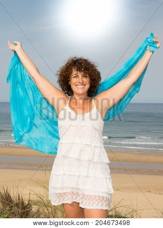 Portrait Of A Carefree Middle Aged Woman Walking Barefoot At The Beach