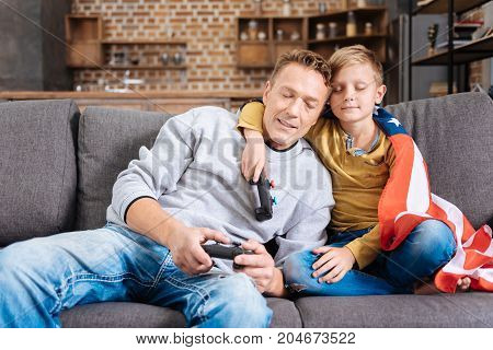 Tired but happy. Pleasant young father and his little son cuddling each other on the sofa, holding game controllers and falling asleep, keeping their eyes closed