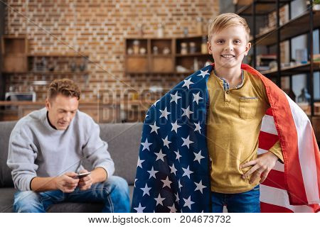 Proud patriot. Cheerful pre-teen boy standing in the living room with an American flag on his shoulders and holding hands on waist, posing for the camera, while his father texting