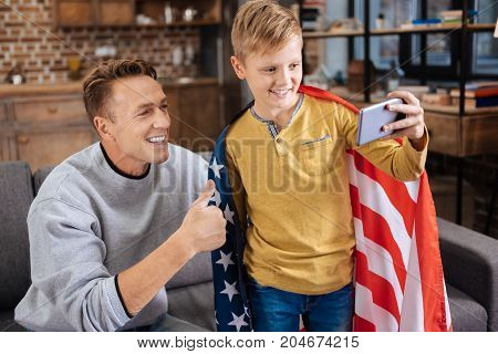 Patriotic family. Charming pre-teen boy wearing a US flag on his shoulders and taking a selfie with his father showing a thumbs up
