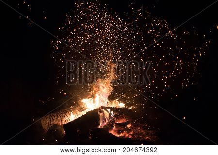 Background of bright orange and red sparks from a campfire at night