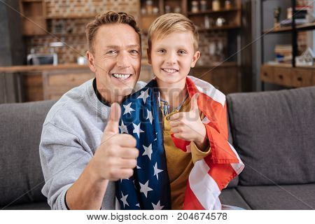 Happy holiday. Cheerful young father and his pre-teen son wearing an American flag sitting on the sofa and smiling at the camera while showing thumbs up