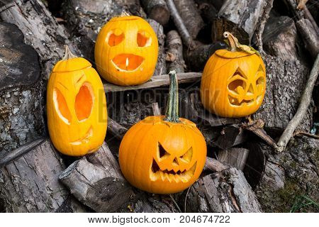 Halloween Themes. Composition Of Four Carved Halloween Pumpkins On Wooden Background. Pumpkins With
