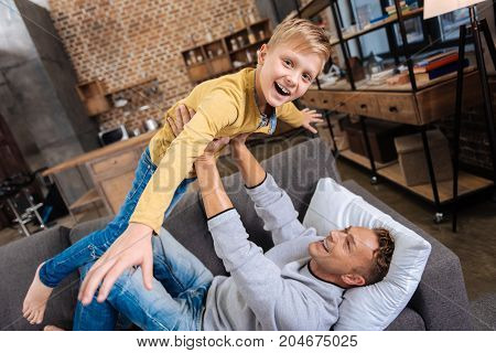 Fun games. Overjoyed pre-teen boy spreading hands wide and being lifted up by his father lying on the sofa, both of them laughing happily