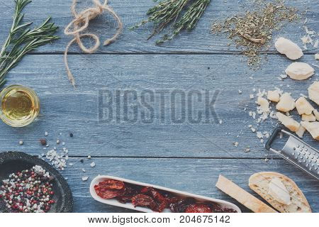 Italian cuisine ingredients background on blue rustic wood, copy space. Cooking healthy food with herbs, mozzarella, parmesan and dried tomatoes, frame, top view